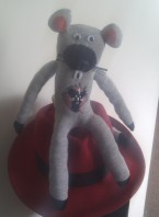 A grey stuffed toy version the rathole radio mascot, propped on top of my Red Hat fedora.